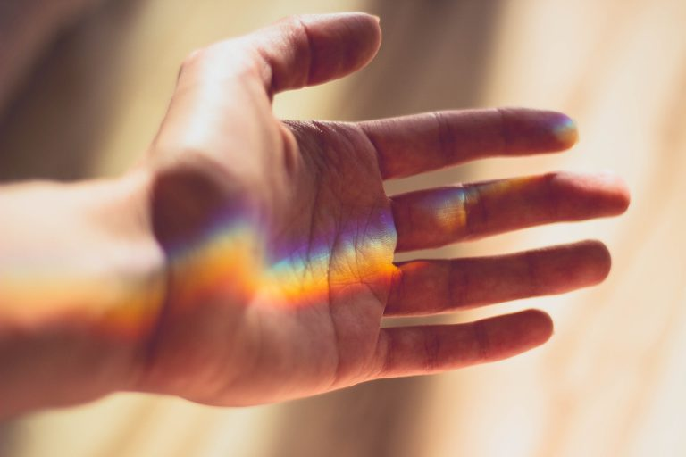 Lightworker hand with rainbow prism reflection