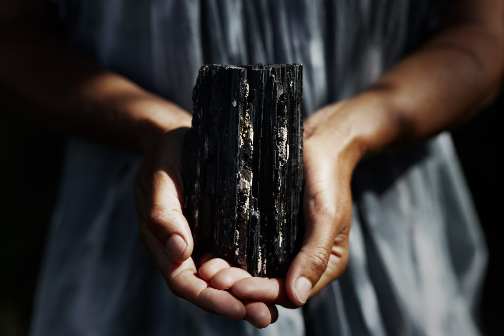Hands holding a chunk of raw black tourmaline, one of the best crystals for protection