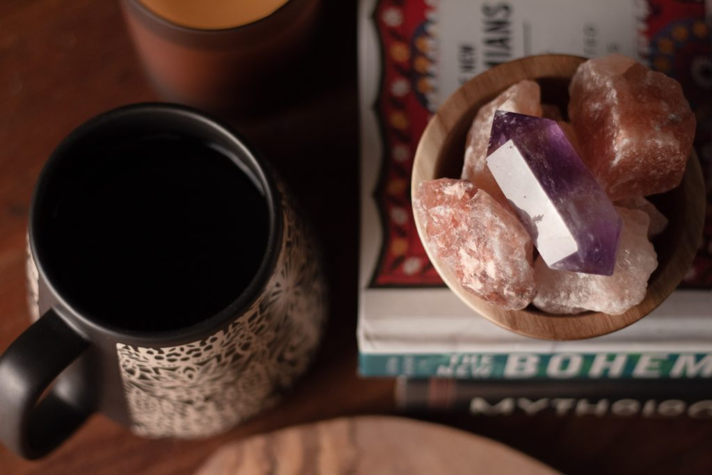 Crystals in a bowl, on top of some books, near a vessel of liquid