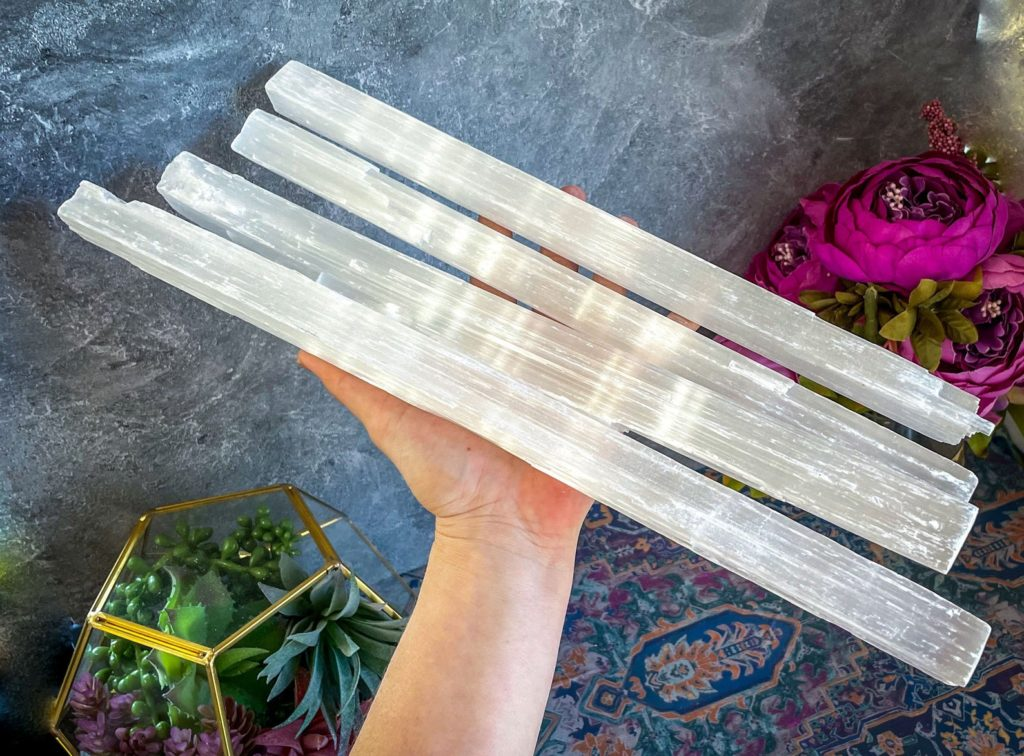 4 large selenite wands held by a human hand